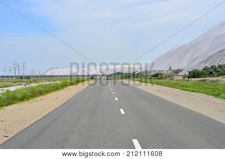 Asphalt road on the edge of the dumps of the mines of Belarus the city of Soligorsk.