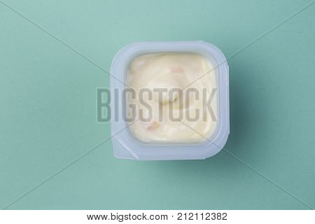 Healthy pale yellow fruit flavored yoghurt with natural coloring in plastic cup isolated on green background - top view