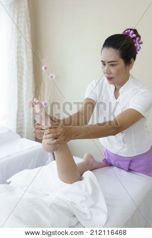 Female professional massager 's hands pressing client's foot for Thai traditional massage in Spa salon