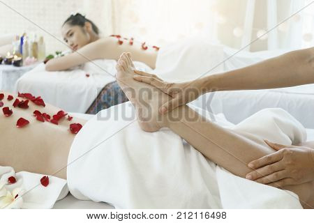 Female professional massager 's hands pressing client's foot and leg for Thai traditional massage in Spa salon