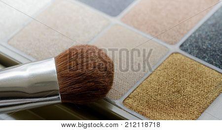 Make up eye shadows set and brush closeup background. Shallow DOF