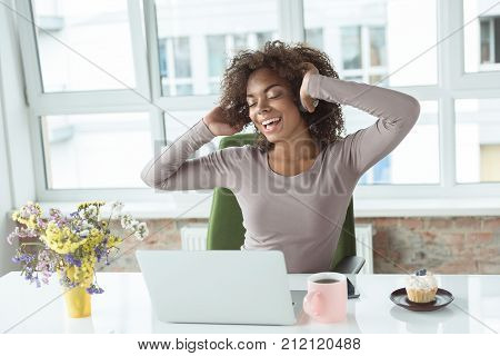 Portrait of cheerful mulatto woman listening music while locating at desk in room. She having job on laptop