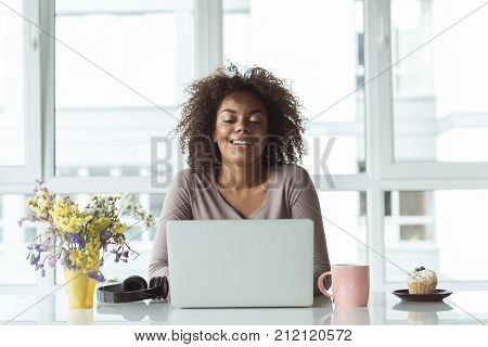 Portrait of outgoing young mulatto female typing on laptop while sitting at desk in office