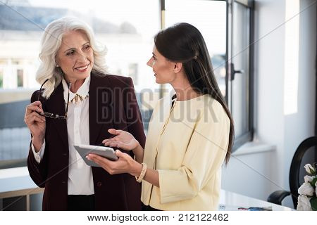Useful gadget. Positive stylish business women are standing in office and expressing gladness while talking to each other. Young girl is holding tablet and showing screen to gray-haired skillful lady