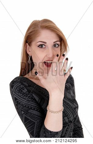 A beautiful woman in a gray dress laughing and holding her hand on her face with big eyes isolated for white background