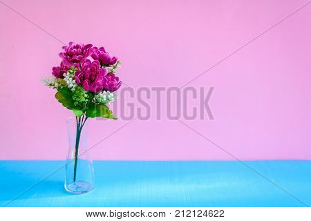 decorate flower in a vase on a blue table and a pink wall background with a color pastel style and text space