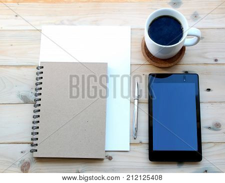 Table top shot of tablet and paper work with black coffee in an office/business style scenario