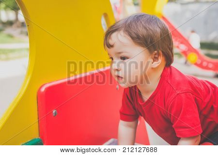 portrait of cute little child in red t-shirt excitedly playing on playground. concept of happy healthy child
