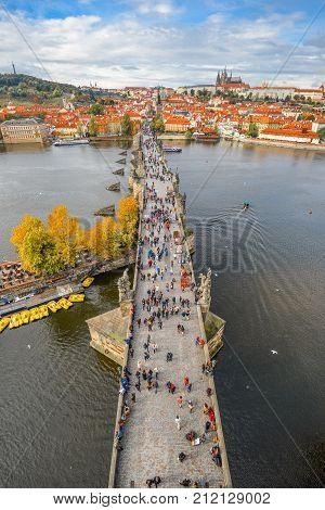 Prague, Czech Republic - October 7, 2017: Top view panorama of ancient Charles Bridge crosses Vltava river in Prague. Tourists are walking Charles Bridge and enjoying golden autumn and dramatic sky