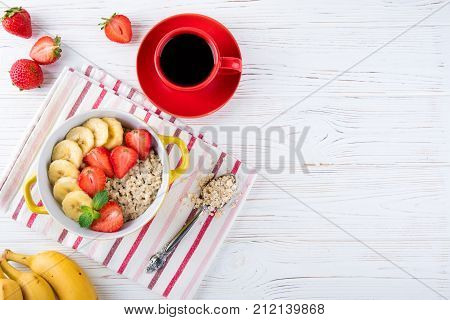 Breakfast oatmeal porridge with fruits berries and coffee cup. Oatmeal with strawberries and banana. Healthy breakfast concept. Top view