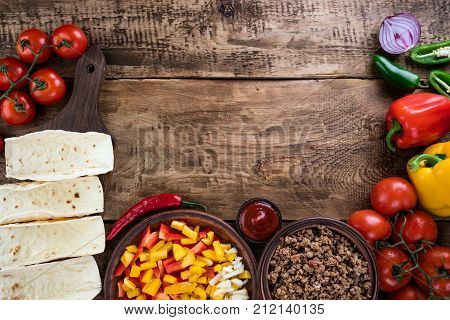 Mexican tacos with vegetables and meat. Ingredient for cooking tacos al pastor on wooden background. Top view. Copy space