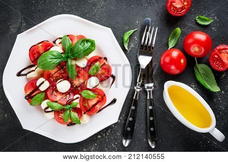 Caprese salad. Tomatoes mozzarella cheese tomatoes olive oil basil herb leaves balsamic sauce on dark background. Italian food. Top view