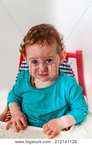 Confused baby making funny offended face in the high chair with rice all over the head - development concept