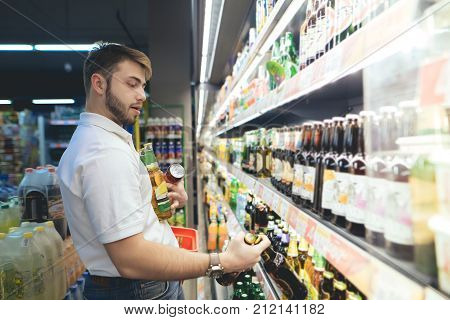 A supermarket buyer takes beer out of shelves. The man got full hands of the beer while shopping in the supermarket