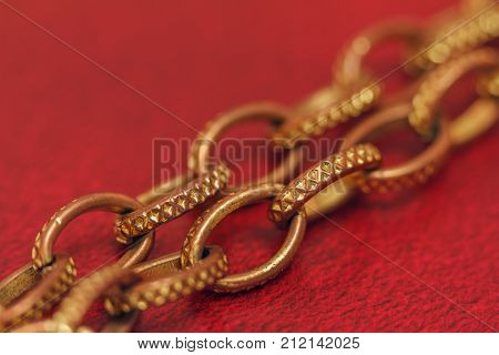 Aureate Chain Close-up On A Red Background