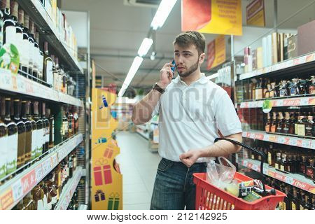 Man choosing a wine bottle in a supermarket. The husband speaks by telephone in the alcologolny department of the supermarket. A man chooses alcohol in a supermarket. Shopping in the store.