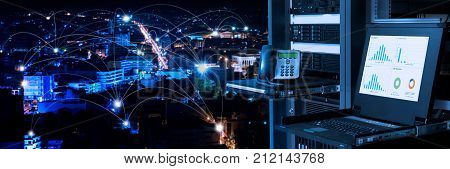 Management and monitoring monitor in data center and connectivity lines over night city background smart city concept