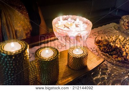 Girl in traditional indian saree sitting with beautiful candles on diwali. A glass bowl of floating candles, golden candles of different heights and dry fruits are clearly visible
