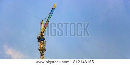 Construction site. Construction cranes and high-rise building under construction against blue sky