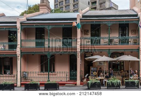 Sydney Australia - March 22 2017: Two-level beige colored historic houses in George Street in The Rocks neighborhood. Balconies and patios One of them is a coffee and tea shop.