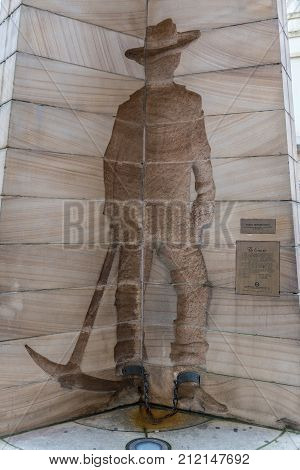 Sydney Australia - March 22 2017: Closeup of The Convict side of three facetted First Impressions Monument at Playfair Street. Beige structure with edges silhouette of man working with pickax.