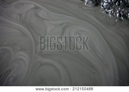 Сolor palette in a puddle of clay. The pattern of liquid mud in a puddle the diamond pipe in the vicinity of Pretoria. South Africa