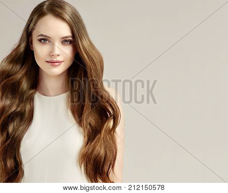 Beautiful model girl with shiny brown straight long  hair in white dress . Care and hair products .