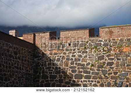 Wall of the fortress with cannons on the backdrop of Table Mountain in Cape town. The strengthening of the Fort in Cape town.