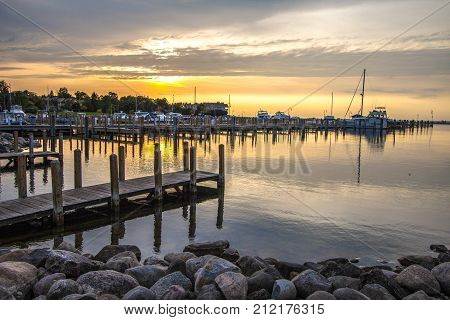 Summer Sunset Over Lake Michigan Harbor.  Wooden dock with a marina and scenic sunset colors at the Great Lakes horizon in Michigan.