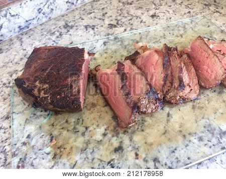 Sliced grilled beef barbecue on the glass cutting board