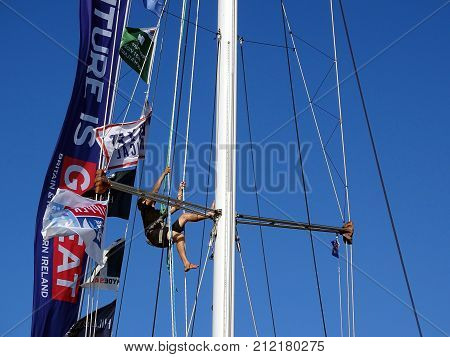 Airlie Beach, Queensland, Australia-January 16, 2016:  A man maintaining equipment up a mast during the Round the World Clipper Yacht Race while at Able Point, Marina
