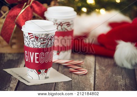 Dallas TX - November 4 2017: Starbucks popular holiday beverage served in the new 2017 designed holiday cups. Displayed with candy canes on wooden rustic table. Christmas hats and sparkling tree lights in the background.