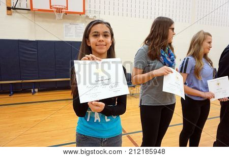 JOLIET, ILLINOIS / UNITED STATES - MAY 11, 2016: Eighth grade students proudly hold certificates of awards that they have earned, in the gymnasium of the Drauden Point Middle School.