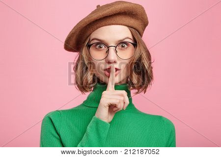Portrait Of Beautiful Young Female Wears Retro Clothes, Puts Fore Finger On Lips As Asks Not To Tell