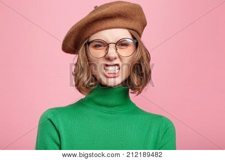 Portrait Of Angry Female Has Own Style Of Clothing, Keeps Teeth Clenched, Frowns Face In Dissatisfac