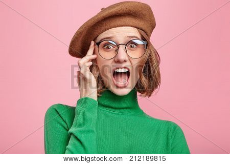 Startled Young Woman Keeps Mouth Widely Opened, Weras Round Glasses, Being Stunned To Notice Awful T