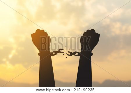 silhouette hand with chain is absent and blurred sky in sunrise background