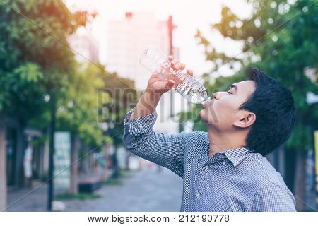 Young asian handsome business man drinking water from bottle in a park