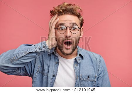 Stupefied Hipster Male Keeps Mouth Widely Open Keeps Hand On Head Being Astonished To Recieve Little