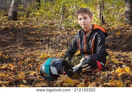 Portrait of a young rider mtb sitting in the forest on a yellow foliage holding a full-face helmet. The concept of outdoor sports for children poster