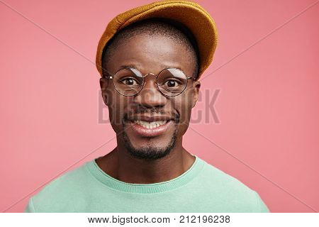 Glad Smiling Hipster Male Wears Fashionable Cap, Glasses, Has Good Mood As Spends Free Time In Merry