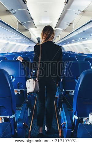 Back view of young woman wearing formal suit walking the aisle on plane.