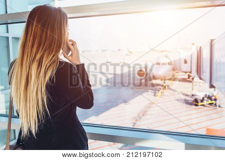 Young businesswoman talking on mobile phone waiting for her flight looking at planes through the window standing in departure zone at airport.