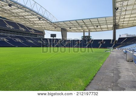 Oporto, Portugal - july 2016: Blue Seatings Green Pitch Gallery and Glass Benches inside Empty Stadium Before Soccer Match