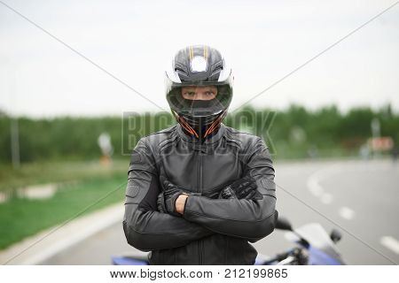 Lifestyle portrait of self determined confident young blue eyed male motorcyclist dressed in stylish leather outfit and helmet standing outdoors next to his motorbike keeping arms crossed