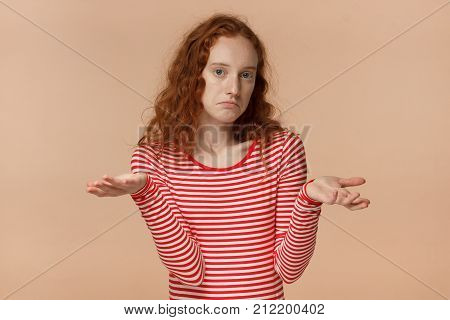 I Don't Know. Attractive Young Redhead Student Being At A Loss, Showing Helpless Gesture With Arm An