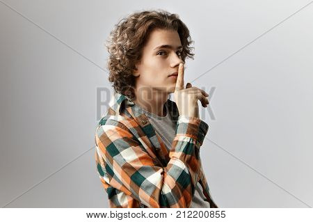 Let's keep it a secret. Fashionable young Caucasian male wearing checkered shirt making silent gesture holding index finger at his mouth. Secrecy mystery and confidential information concept