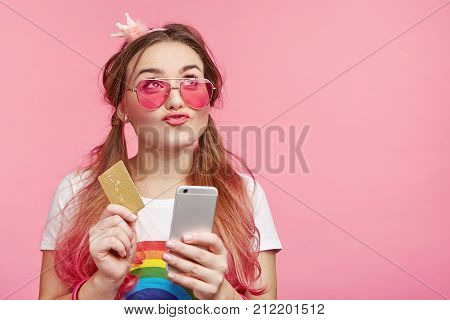 Dreamful Adorable Female Holds Smart Phone And Plastic Card, Does Shopping Online, Dreams About New