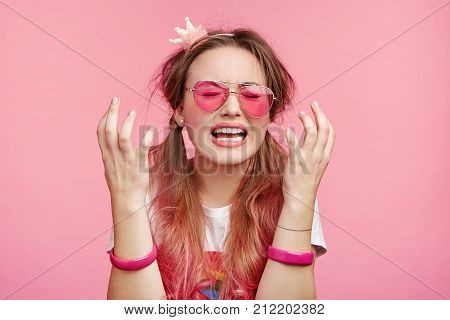 Desperate Female Wears Pink Glasses, Gestures In Puzzlement, Being Depressed As Has No Money For Goi
