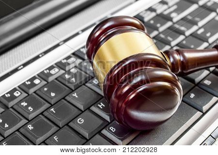 Judge's wooden gavel on laptop keyboard. Close up. Online auction and law concept.